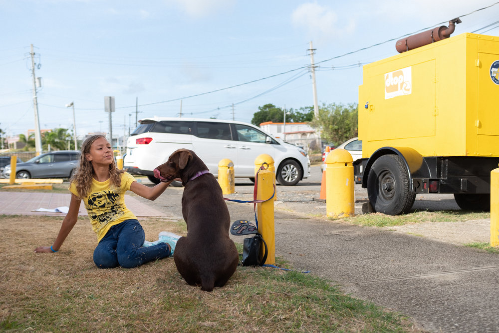 Girl playing with her dog near the clinic, Ceiba