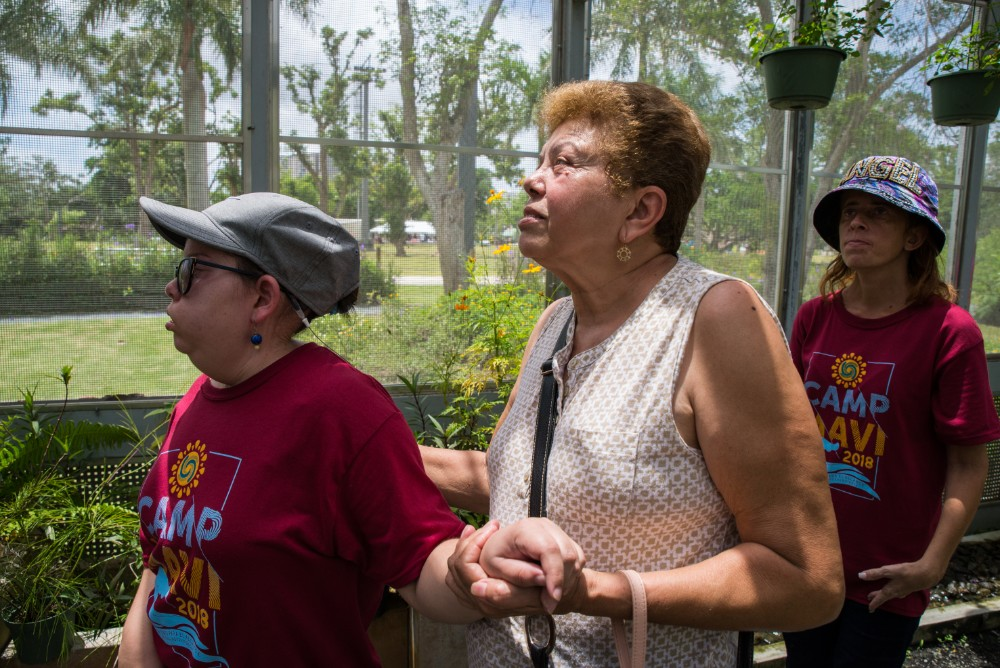 The parent of a Camp MAVI client supports her as they walk through the butterfly enclosure.