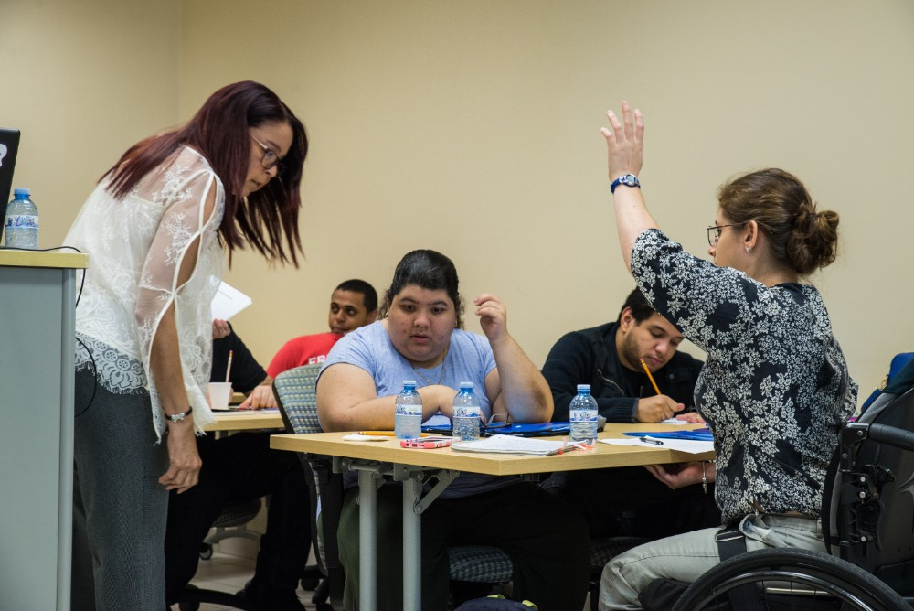 """A student raises her hand to answer a question during a Leadership Academy lesson on """"Sunshine Laws"""""""