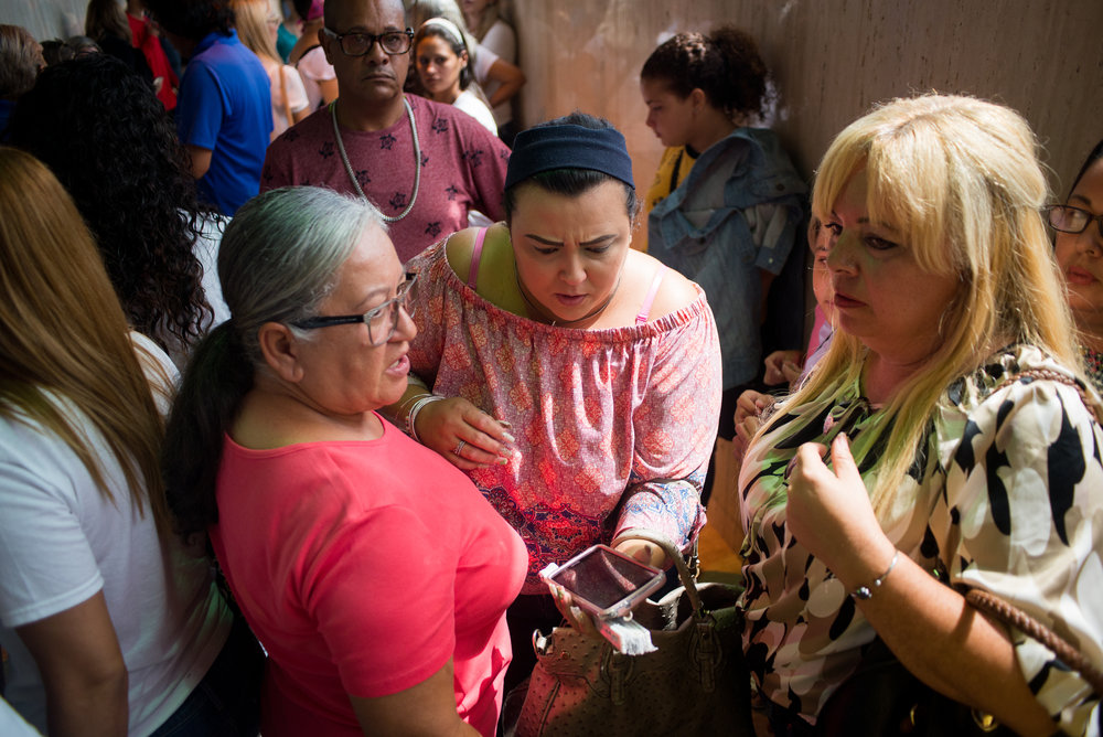 6/11/18 – Arecibo, Puerto Rico – Families and teachers of schools that are to be closed before the Fall 2018 academic year wait in the Judicial Center of Arecibo for the public hearing from the Department of Education about their reasonings for closing schools. The Puerto Rican Department of Education is closing 283 schools, and moving multiple schools into the same building, citing the past year's drastic drop in enrollment as one of the primary reasons to lower the amount of schools, and instead increase the amount of students in each school. Students of special education schools are one of the groups to be most negatively affected by these closings, as the new schools may not offer the resources the students need and have access to at their current schools. (Sofie Hecht Photography)